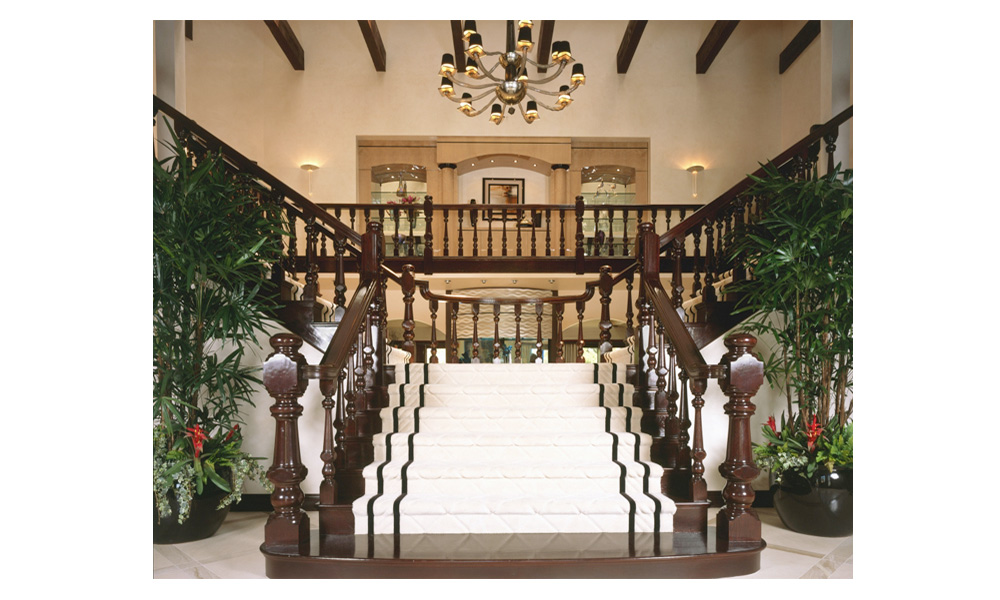 dramatic double staircase entry, grand entry, split entry staircase, formal staircase, custom white staircase runner, exposed beams, staircase chandelier, dark wood railing