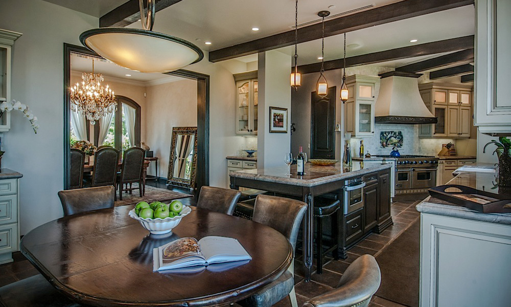 elegant chandelier, dark wood beams, traditional kitchen, antique brown floor tile, cozy kitchen, brown leather dining chairs, antique wood kitchen table, kitchen lighting, spacious kitchen